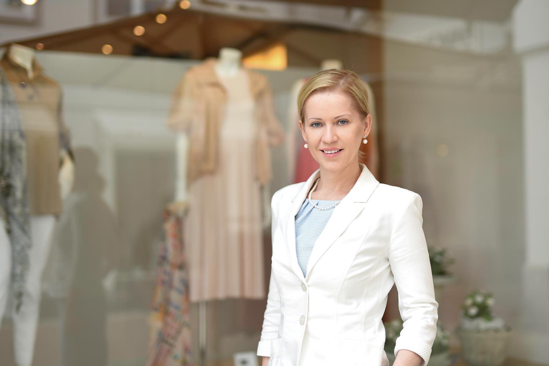Janine Katharina Pötsch Knigge Trainerin München - vor einem exklusiven Modegeschäft